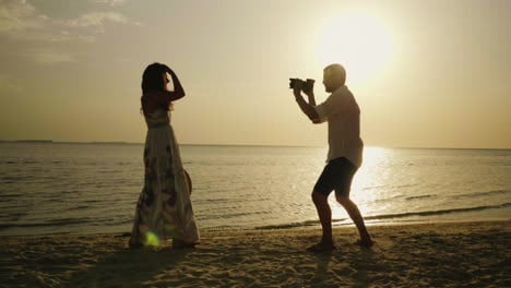 Silhouette-Of-A-Male-Photographer-On-The-Beach-He-Is-Photographing-A-Young-Woman-4k-Video
