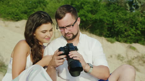 A-Young-Couple-Looks-At-The-Pictures-On-A-Digital-Camera-Sit-Next-To-The-Beach-Great-Memories-From-H