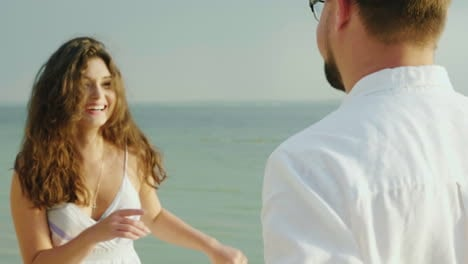Young-Woman-With-Her-Husband-Dancing-On-The-Beach