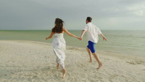 Young-Couple-In-Love-In-Light-Clothes-Carefree-Running-On-A-Clean-Tropical-Beach