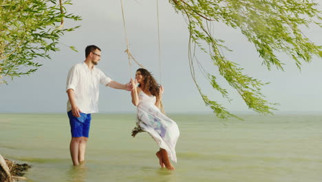 A-Young-Man-Is-Rolling-His-Girl-On-A-Swing-Against-The-Background-Of-The-Sea-In-The-Rain-Romance-And