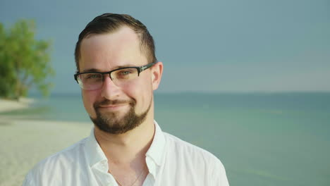 Portrait-Of-A-Young-Man-On-A-Tropical-Beach-In-An-Easy-Shirt-He-Smiles-And-Looks-Into-The-Camera-Wea