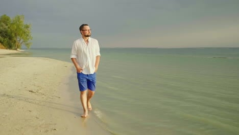 A-Young-Well-Looking-Man-In-Light-Clothes-And-Glasses-Goes-Along-The-Beach-Along-The-Sea-Escape-From