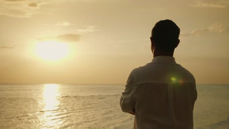 Lonely-Man-Looking-Forward-To-The-Sunset-Over-The-Sea-Back-View-Romance-And-Vacation-At-Sea