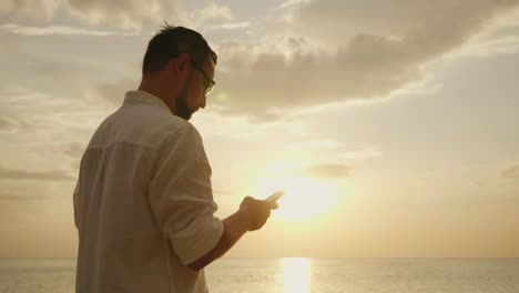 A-Young-Man-On-Vacation-Near-The-Sea-Using-A-Smartphone-At-Sunset-4k-Slow-Motion-Video