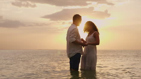Young-Couple-In-Love-Standing-In-The-Sea-At-Sunset-Looking-At-Each-Other-Hd-Video