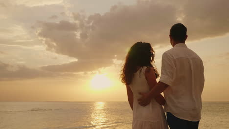Young-Couple-In-Love-Embraces-Look-Together-Forward-To-The-Sunset-By-The-Sea-Back-View-Hd-Video