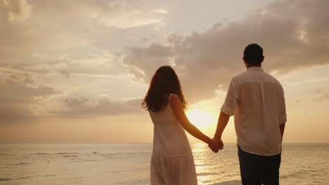 Young-Loving-Couple-Holding-Hands-Stand-In-The-Water-And-Look-At-The-Sunset-Over-The-Sea-4k-Video
