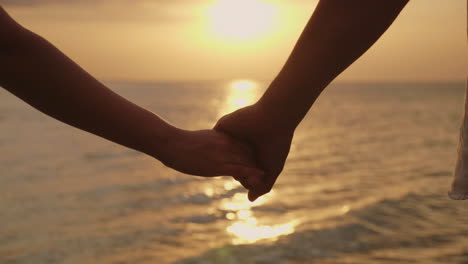 Hands-Of-A-Man-And-A-Woman-Against-The-Background-Of-The-Sea-And-The-Setting-Sun-4k-Slow-Motionvideo