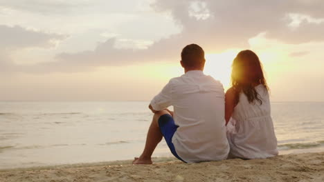 A-Man-And-A-Woman-Are-Sitting-Side-By-Side-On-The-Sand-On-The-Beach-Together-They-Look-At-The-Sunset