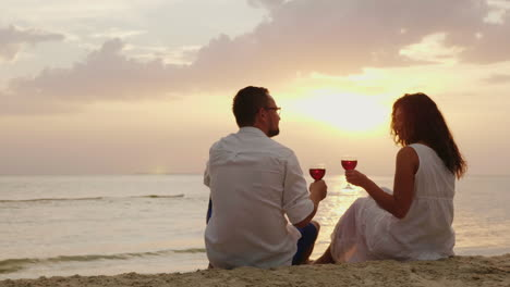 A-Young-Couple-Is-Drinking-Wine-By-The-Sea-At-Sunset-They-Sit-On-The-Sand-Clink-Glasses-Anniversary-