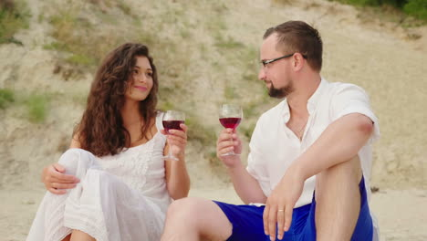 A-Young-Couple-Is-Drinking-Wine-By-The-Sea-At-Sunset-They-Sit-On-The-Sand-Clink-Glasses-Anniversary