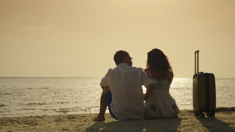 Arrival-On-Vacation-A-Young-Couple-Is-Sitting-On-The-Sand-Near-Their-Travel-Bag-Enjoying-The-Sunset-
