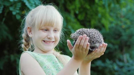 Happy-Blonde-Girl-Holding-A-Hedgehog-Protection-And-Care-Of-Animals-Concept-Slow-Motion-Video