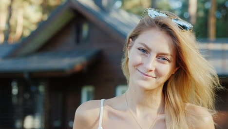 Portrait-Of-A-Young-Attractive-Woman-On-The-Background-Of-Her-House