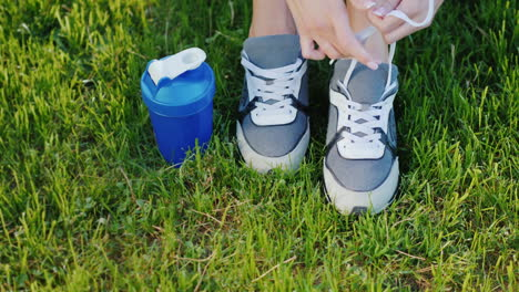 Tie-Shoelaces-On-Sports-Shoes-Female-Legs-On-A-Green-Lawn-Near-A-Bottle-For-Water-Ready-For-An-Activ