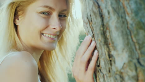 Portrait-Of-A-Beautiful-Young-Woman-Standing-By-The-Tree-In-The-Sun-Smiling-Looking-At-The-Camera-Co