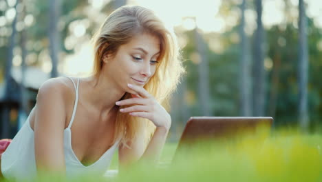 Young-Attractive-Woman-Communicates-On-Video-Chat-Uses-A-Laptop-Lies-On-The-Lawn-In-The-Backyard-Of-