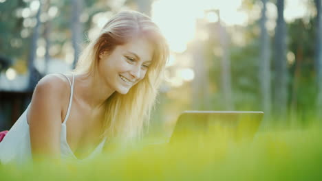 Beautiful-Young-Woman-Enjoys-A-Laptop-Lies-On-The-Lawn-In-The-Backyard-Of-The-House-In-The-Sun-At-Su
