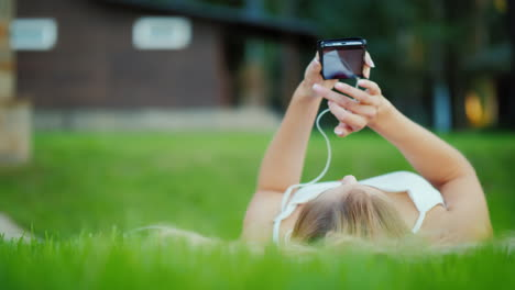 A-Young-Girl-Is-Lying-On-Her-Back-On-The-Lawn-Enjoying-A-Smartphone-Video-With-Shallow-Depth-Of-Fiel