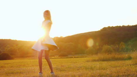Young-Woman-In-A-Light-Dress-Whirls-On-A-Field-In-The-Rays-Of-A-Sunset-Slow-Motion-Video