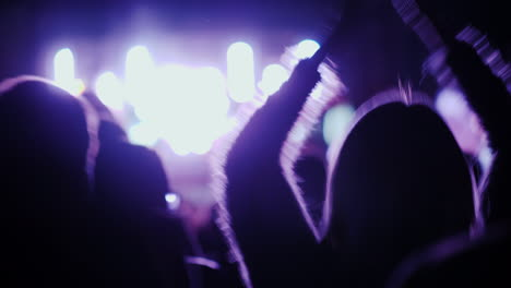 Fans-Are-Dancing-At-A-Rock-Concert-Visible-Silhouettes-Rear-View-4k-10-Bit-Video