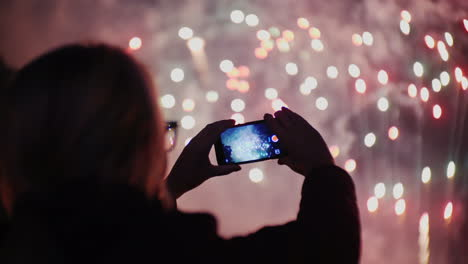 A-Woman-Admires-The-Fireworks-In-The-Night-Sky-Take-Pictures-With-Your-Smartphone