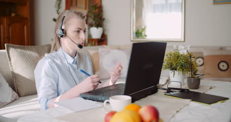 Sales-Representative-In-Headset-Speaking-To-Client-And-Making-Video-Conference-Call-On-Laptop-11