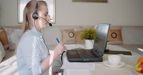 Sales-Representative-In-Headset-Speaking-To-Client-And-Making-Video-Conference-Call-On-Laptop-12
