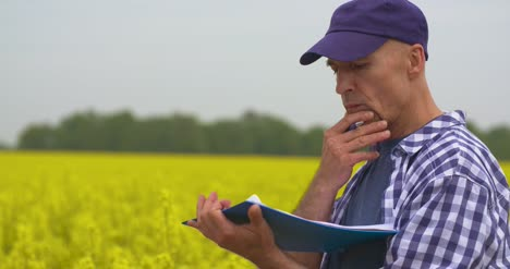 Agriculture-Farmer-Taking-Notes-At-Rapeseed-Field