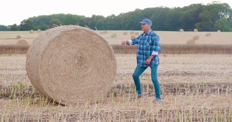Smiling-Farmer-Rolling-Hay-Bale-And-Gesturing-In-Farm-5