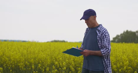 Farmer-Taking-Notes-At-Rapeseed-Field