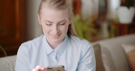 Happy-Woman-Browsing-Smartphone-At-Home