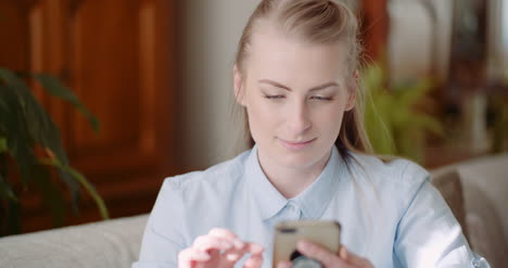 Happy-Woman-Browsing-Smartphone-At-Home-1