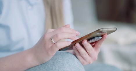 Happy-Woman-Browsing-Smartphone-At-Home-5