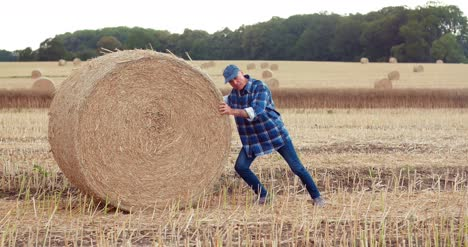 Farmer-Struggling-While-Rolling-Hay-Bale-At-Farm