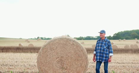 Smiling-Farmer-Rolling-Hay-Bale-And-Gesturing-In-Farm-7