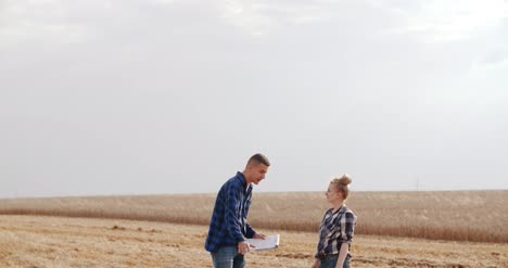 Agriculture-Female-And-Male-Farmers-Talking-At-Wheat-Field-During-Harvesting-18
