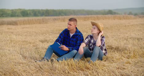 Agriculture-Female-And-Male-Farmers-Talking-At-Wheat-Field-During-Harvesting-2
