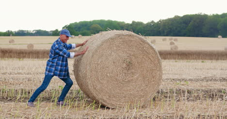 Farmer-Struggling-While-Rolling-Hay-Bale-At-Farm-2