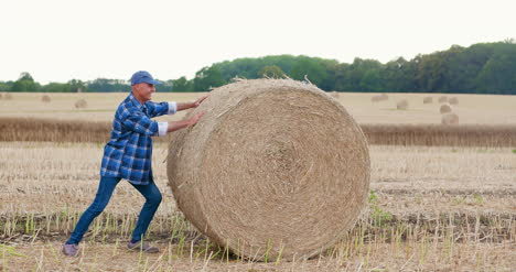 Farmer-Struggling-While-Rolling-Hay-Bale-At-Farm-3
