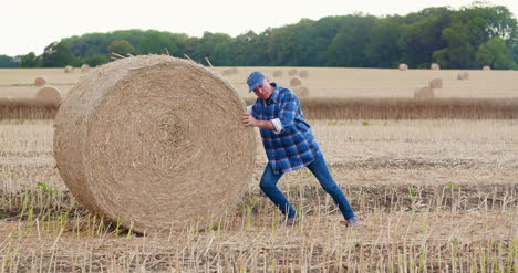 Farmer-Struggling-While-Rolling-Hay-Bale-At-Farm-4