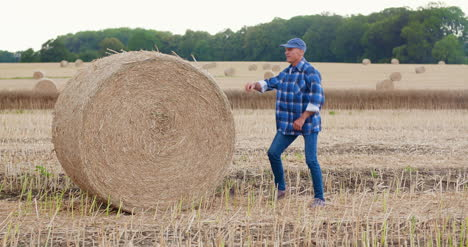Farmer-Struggling-While-Rolling-Hay-Bale-At-Farm-5
