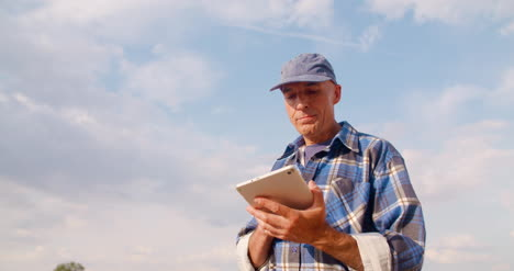 Farmer-Using-Digital-Tablet-At-Farm-Against-Blue-Sky-And-Clouds-9
