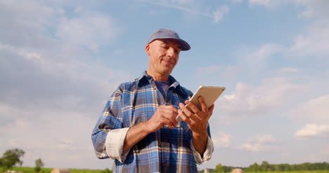 Farmer-Using-Digital-Tablet-At-Farm-Against-Blue-Sky-And-Clouds-10