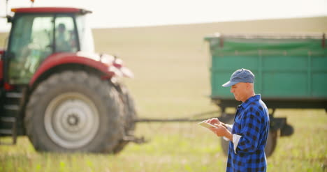 Farmer-Using-Digital-Tablet-While-Looking-At-Tractor-In-Farm-13