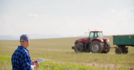 Farmer-Using-Digital-Tablet-While-Looking-At-Tractor-In-Farm-16
