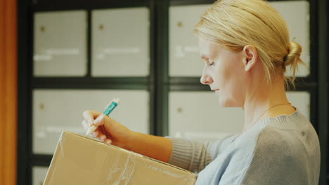 A-Woman-Writes-An-Address-On-The-Parcel-Box-In-The-Post-Office