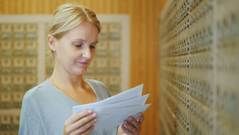 Attractive-Woman-Looks-Through-Letters-In-The-Post-Office-On-The-Background-Of-Mailboxes