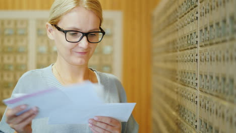 Portrait-Of-A-Young-Stylish-Woman-With-A-Bundle-Of-Letters-In-Her-Hands-In-The-Post-Office